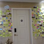 Wall outside the rooms filled with messages and polaroids of guests