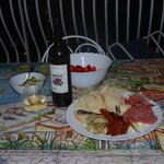 Antipasti plate, wine and fresh strawberries from local market