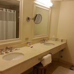 Spacious bathroom with double sinks, makeup mirror and stool