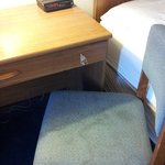 Stained chair and scuffed particle board desk