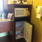 bathroom sink area with microwave, fridge and coffee maker
