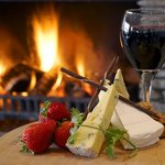 A glass of wine and some snacks by the fireplace