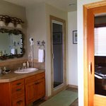 Bathroom of the Woodland Room (comfy jacuzzi tub, double-sided gas fireplace, steam shower, and