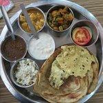 That's the hot selling thali comprising the lachcha paranthas, paneer, aloo gobi, dal, raita..