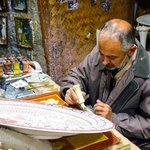 Multiple generations on the job - this man is painting an intricate family pattern