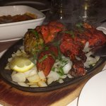 Tandori mixed grill with a chicken madras in the background. sizzling hot.
