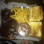 Delicious ribs platter with baked beans, French fries and toast.