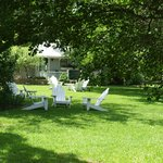 Part of the manicured grounds with tall, old oak trees and seating to slow down and visit with o
