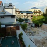 View from balcony of room 212 overseeing the pool and also the neighbouring buildings and constr