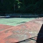 Quadra de tênis em péssimo estado de conservação.