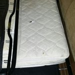 Disgusting mattress with gum wrapper and debris underneath. Twin size mattress on a queen sized
