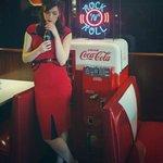 50s model next to an an original Coke dispenser