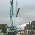 A huge crane lifts individual timbers
