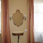 Красивое зеркало под старину между двумя окнами в номере