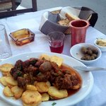 Naxian sausage with potatoes, olives, wine, bread and garlic butter