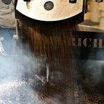 Frisch gerösteter Kaffee verläßt die Röstmaschine