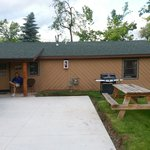 Parking pad with gas grill and picnic table outside front door of cabin