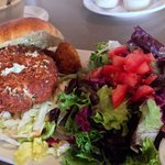 Crab cake sandwich with side salad and hush puppies.