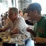 the guys enjoyed their oysters, oblivious to the server, because they were mezmerized by the oys