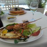Fresh grilled lobster in the foreground, seafood risotto at back.