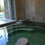 Jacuzzi intérieur avec porte fenêtre ouvrant sur la piscine