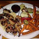 Bacon wrapped shrimp with sweet potato fries and grilled veggies.