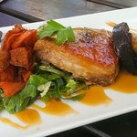 Slow braised pork belly with sweet potato, greens and black pudding.