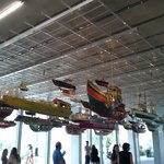 A suspended sculpture of multiple boats suspended from the main lobby ceiling