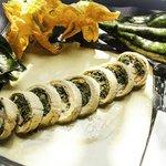Rollo de pollo, rellena de flor de calabaza y espinacas con crema de chile poblano y avellanas.