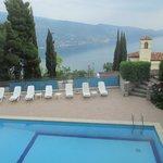 Zicht vanuit de eetzaal op zwembad en Gardameer
