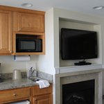 Kitchen area next to TV and electric fireplace