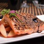 Kahi Sake: salmón con costra de semilla de cilantro y pimienta negra a la plancha, duraznos deli