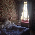 Room with a bow window and exquisite tapestry