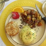 Eggs benedict with home fries and bacon