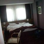 Chambre, avec le lit contre la baie vitrée.