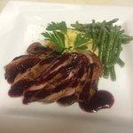 Duck with dark cherry reduction sauce, creamy polenta and haricot vert.