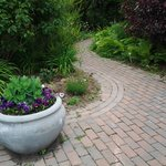 Beautiful stone pathways with casually landscaped plantings to give an old garden appeal.