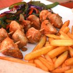 Chicken skewers with vegetables and French fries.