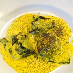 Homemade ravioli filled with fish in saffron souce
