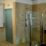 Open shower and glass toilet room door