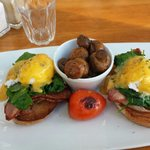 Eggs benedict with bacon, and mushrooms on the side.