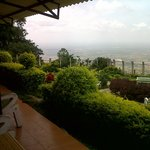 VIEW OF THE VALLEY AND FLATS BELOW FROM THE PORCH OF THE 3 STUDIO ROOMS AT HOTEL MAYURA, NANDI H