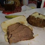 Tri-tip Sandwich, baked potato and pickle spear.