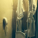 Robes and slippers hang over toilet