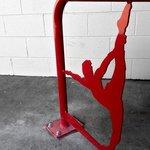 Custom yoga-themed bike rack in front of the studio showing female silhouette in dancer pose.
