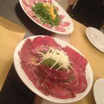 (Front dish) Beef Carpaccio with Rocket and Parmesan, (back dish) Smoked duck fillet with orange