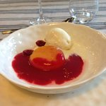 Homemade vanilla ice cream with poached peach and raspberry sauce