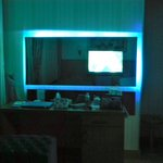 Unusual feature of neon lights behind vanity mirror...that housed the TV also.