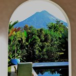 Room with private pool, view of Arenal framed by patio archway.