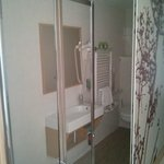 The shower and bathroom divided from the room by sliding doors